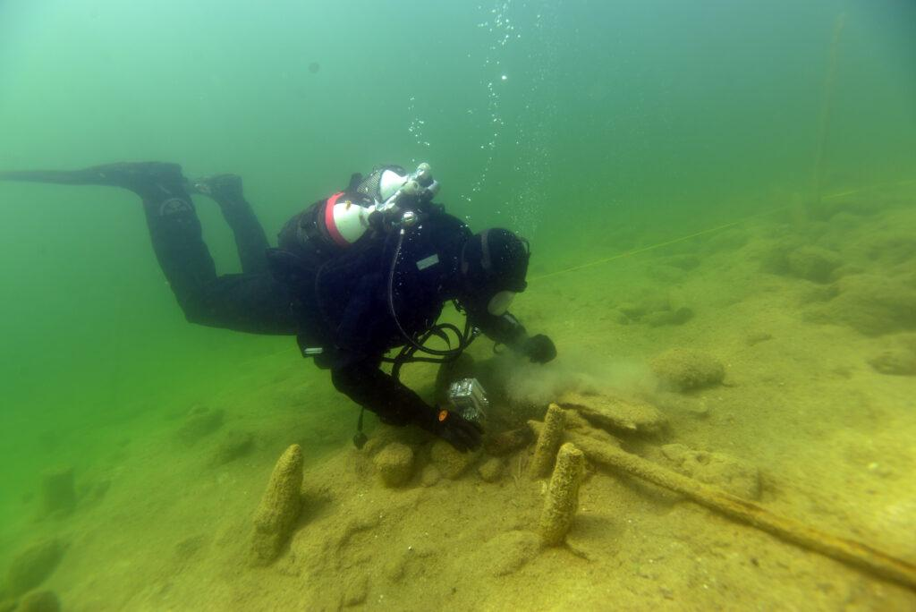 Unterwasser Taucher überprüft das Welterbe Pfahlbauten in Österreich